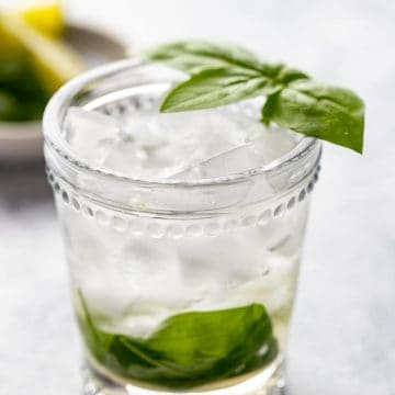 Single glass of basil and lime vermouth cocktail with a basil leaf garnish and limes in the background.