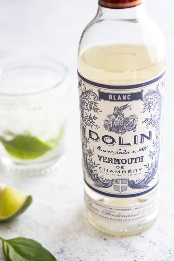 Bottle of Dolin blanc vermouth with a glass in the background with lime and basil.