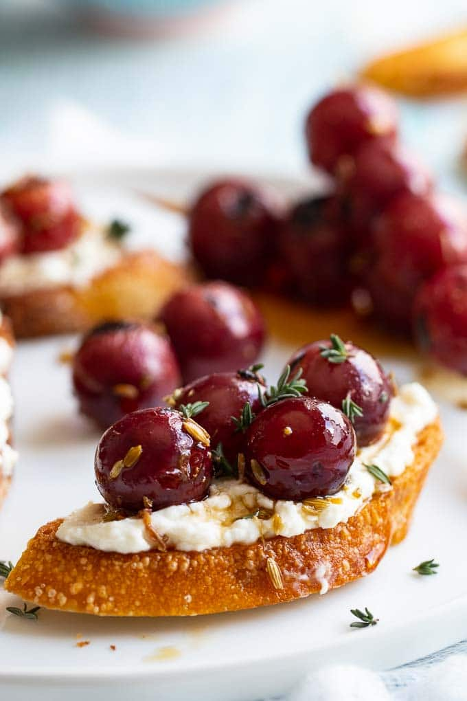 Close up of a gilled baguette slice topped with whipped ricotta and  red grapes garnished with fresh thyme.