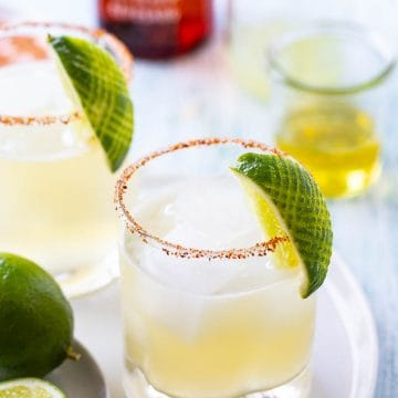 Two margaritas on the rocks with a lime garnish on a white platter.