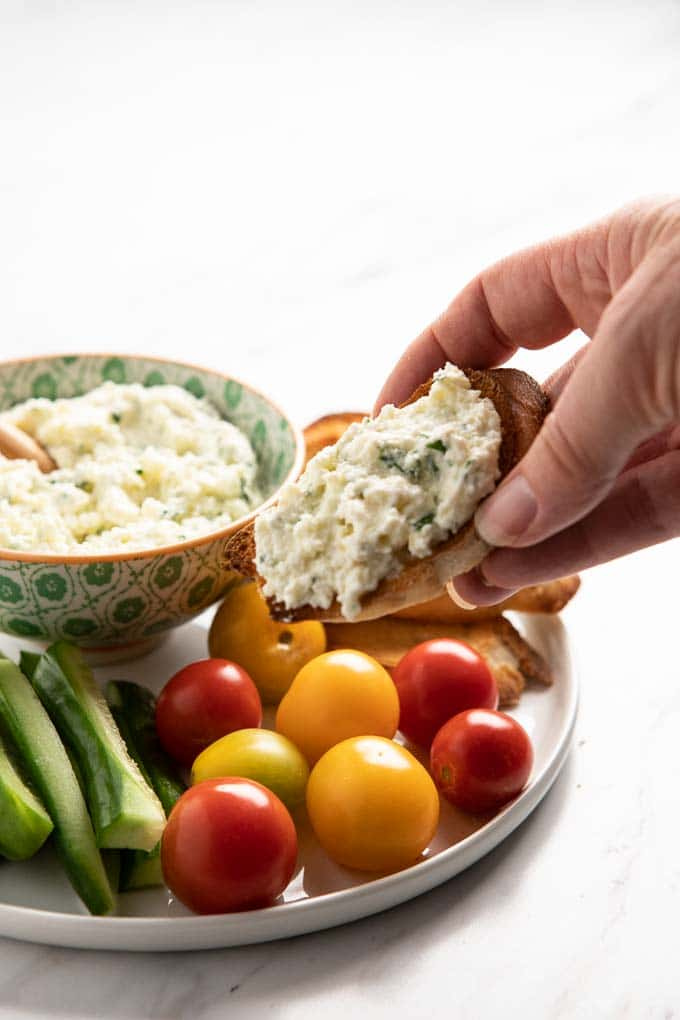 Bowl of whipped ricotta spread on a baguette slice with a bowl of whipped ricotta and vegetables in the background.