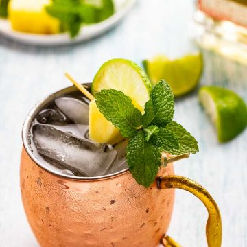 Copper mug of Mexican Mule - a tequila and ginger beer drink with a garnish of lime, pineapple and mint.