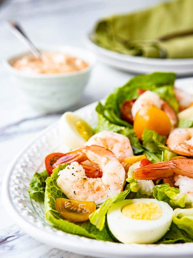 Angled shot of Shrimp Louie Salad on a platter with a bowl of louie dressing on the side.