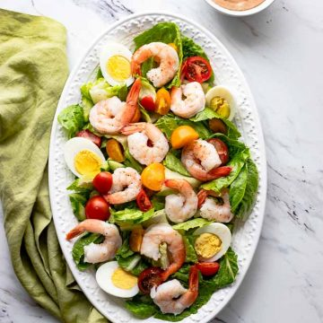 Overhead shot of Shrimp Louie Salad with a side of dressing.