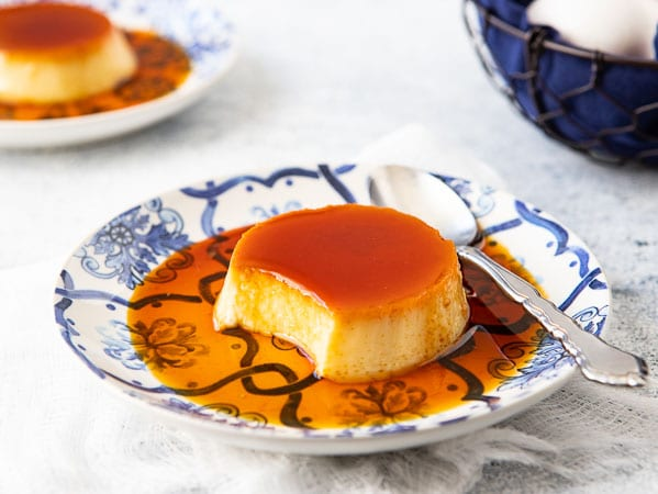 Close up of traditional  Spanish flan recipe with a portion removed to show the inside of the flan.