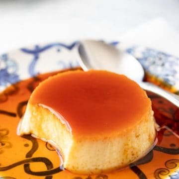 Close up photo of Spanish flan recipe with a portion removed to show the interior.