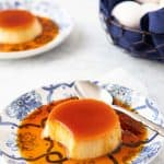 Single serving on spanish flan with caramel sauce and a spoon.