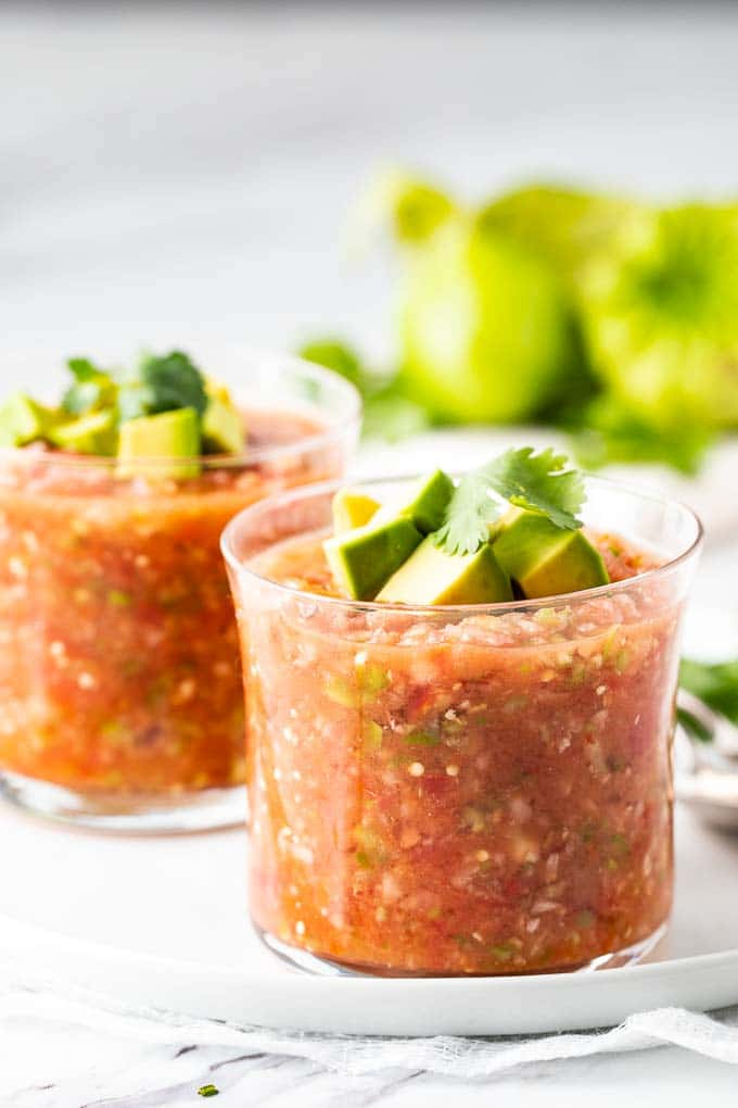 two glasses of an easy gazpacho recipe garnished with avocado and cilantro.