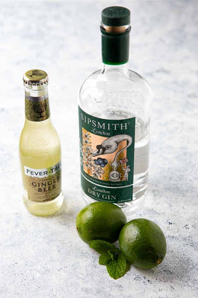 Ingredients needed for the gin mule recipe - gin, ginger beer, limes and fresh mint.