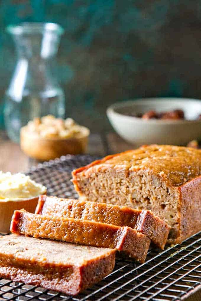 Date Nut Loaf recipe on a cooling rack with several cut slices next to a pot of butter.