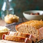 Date Nut bread recipe on a cooling rack with several cut slices next to a pot of butter.