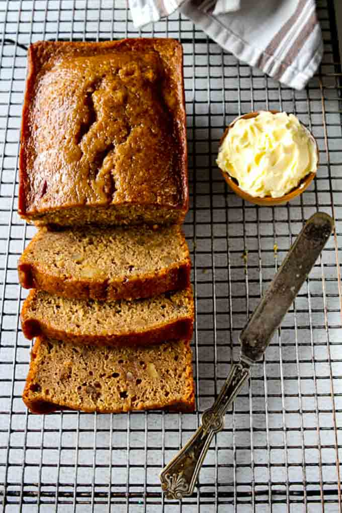 Loaf of sliced date nut bread on a cooling rack with a knife and pot of butter.
