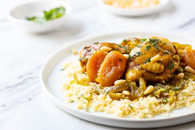 Close up photo of this Moroccan Chicken stew recipe on a plate with plain couscous underneath.