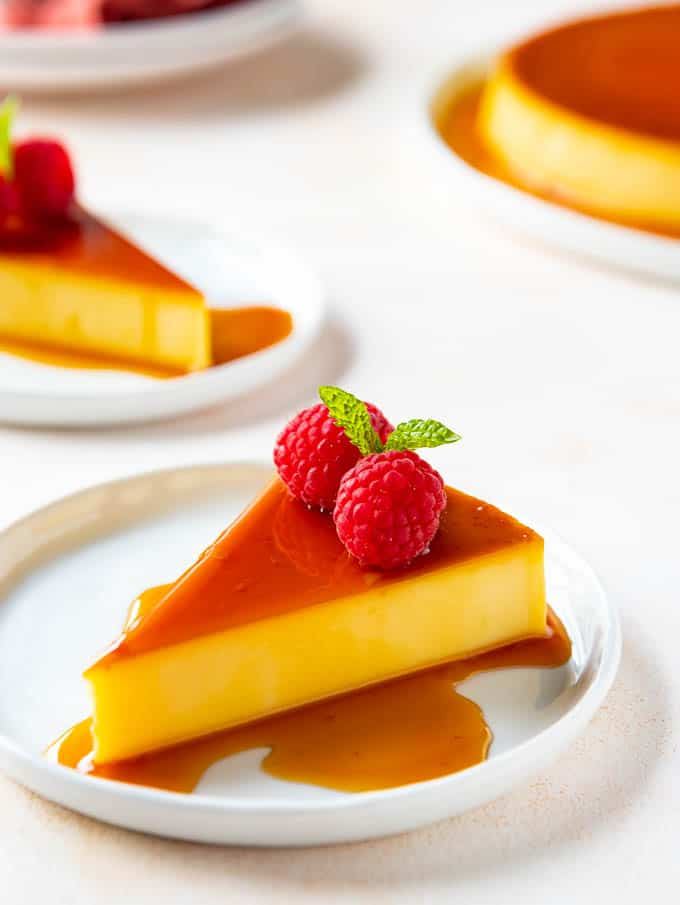 A slice of Mexican Flan on a plate with fresh raspberries and mint garnish.