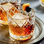 Two rocks glasses on a tray with a bourbon manhattan and a cherry and orange peel garnish.