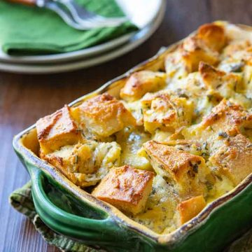 savory bread pudding recipe in a casserole dish with plates and silverware in the background.