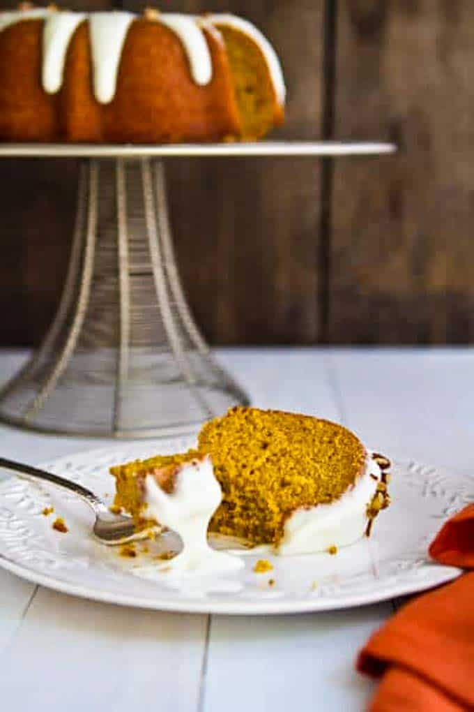 bourbon pumpkin bundt cake with bourbon cream cheese frosting on a plate with a fork.