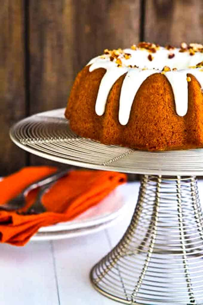 Bourbon Pumpkin bundt cake on a cake stand with plates  in the background.