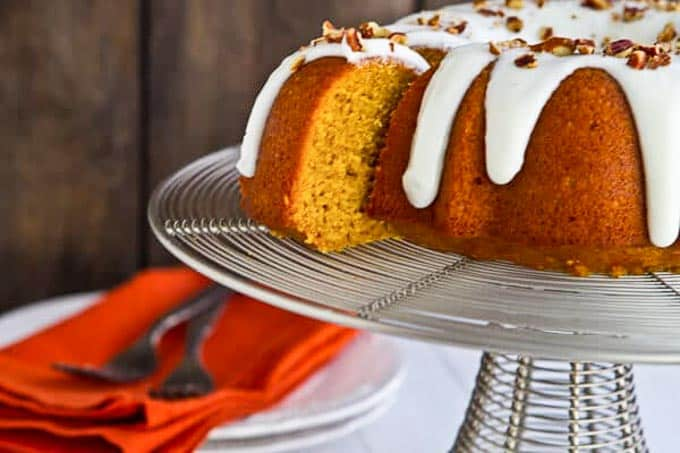 Bourbon Pumpkin Bundt cake for Thanksgiving on a cake stand with a slice pulled out.