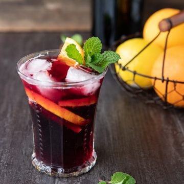 A glass of tinto de verano on a table with lemons and oranges in the background.