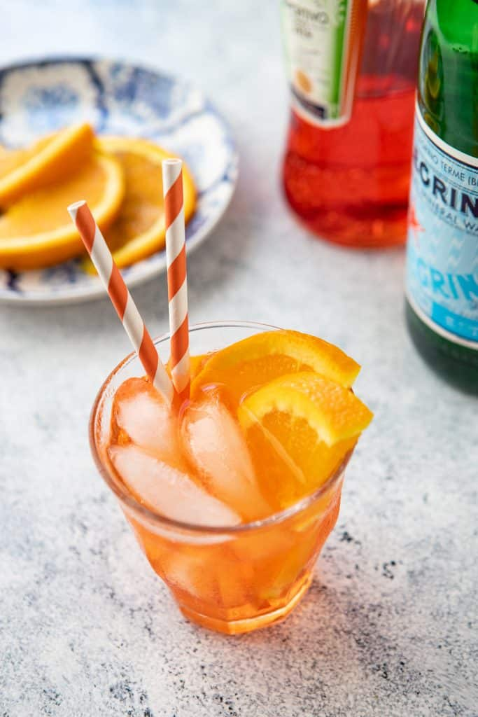 Glass of Spritz Veneziano with orange slices in the background