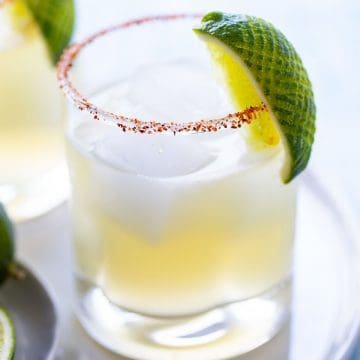 A glass of the best margarita on the rocks with a lime garnish.
