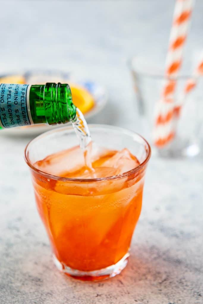 Sparkling water being poured into a glass with aperol and prosecco