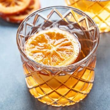 Single glass of a Bourbon Old Fashioned with an orange garnish.